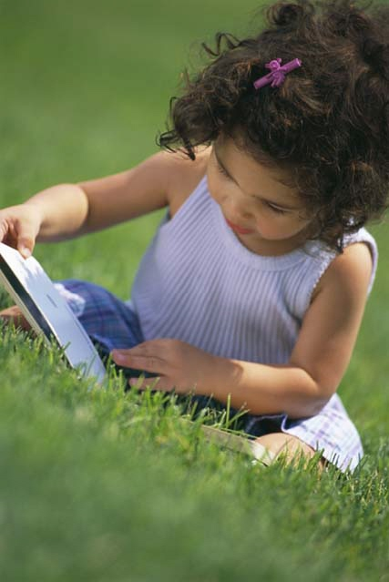 Little girl sitting on the grass reading a book